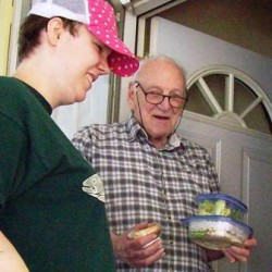 Volunteer Gloria delivering meal to Meals on Wheels client.